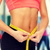 close up of female hands measuring waist stock photo © dolgachov