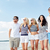 smiling friends in sunglasses walking on beach stock photo © dolgachov
