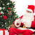 santa claus with smartphone and christmas tree stock photo © dolgachov