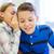 smiling schoolgirl whispering to classmate ear stock photo © dolgachov