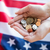 close up of hands with coins over american flag stock photo © dolgachov