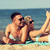 happy couple with modern gadgets lying on beach stock photo © dolgachov