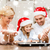 happy family in santa helper hats making cookies stock photo © dolgachov