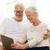 happy senior couple with tablet pc at home stock photo © dolgachov