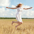 happy young woman jumping on cereal field stock photo © dolgachov