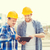 smiling builders in hardhats with tablet pc stock photo © dolgachov