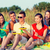 smiling friends sitting on summer beach stock photo © dolgachov