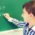 little smiling schoolboy writing on chalk board stock photo © dolgachov