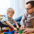 father and son playing with toy blocks at home stock photo © dolgachov