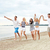 smiling friends in sunglasses running on beach stock photo © dolgachov