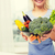 close up of woman holding vegetables in bowl stock photo © dolgachov