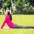 smiling woman doing exercises on mat outdoors stock photo © dolgachov