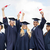 happy students in mortar boards waving diplomas stock photo © dolgachov
