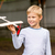 smiling little boy holding a wooden airplane model stock photo © dolgachov