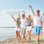 smiling friends walking on beach and waving hands stock photo © dolgachov
