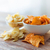 close up of potato crisps and nachos in glass bowl stock photo © dolgachov