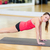 smiling woman doing plank on mat in gym stock photo © dolgachov