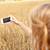 close up of girl with smartphone on cereal field stock photo © dolgachov