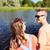 happy teenage couple sitting on river berth stock photo © dolgachov