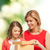 smiling mother and daughter opening gift box stock photo © dolgachov