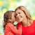 happy daughter whispering gossip to her mother stock photo © dolgachov