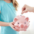 close up of girl with piggy bank putting coin stock photo © dolgachov