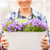 close up of happy woman holding flowers in pot stock photo © dolgachov
