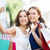 happy women with shopping bags and smartphone stock photo © dolgachov