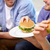 close up of friends eating hamburgers at home stock photo © dolgachov