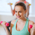 smiling woman with dumbbells exercising in gym stock photo © dolgachov