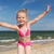 happy little girl in swimwear having fun on beach stock photo © dolgachov