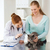 happy woman with cat and doctor at vet clinic stock photo © dolgachov