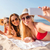 group of smiling women with smartphone on beach stock photo © dolgachov