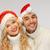 family couple in sweaters and santas hats stock photo © dolgachov