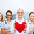 smiling female doctor and nurses with red heart stock photo © dolgachov