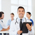happy doctor with clipboard over medical team stock photo © dolgachov