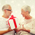 happy senior couple with gift box at home stock photo © dolgachov