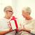 happy senior couple with gift box at home stock photo © dolgachov