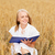 smiling young woman reading book on cereal field stock photo © dolgachov