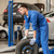 mechanic with wheel tire at car workshop stock photo © dolgachov