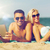 happy couple with tablet pc sunbathing on beach stock photo © dolgachov