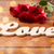 close up of diamond ring red roses and word love stock photo © dolgachov