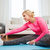 happy woman stretching leg on mat at home stock photo © dolgachov