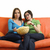 female friends eating popcorn and watching tv at home stock photo © dotshock
