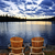 wooden chairs at sunset on lake shore stock photo © elenaphoto