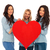 3 smiling women offering their big red heart to you stock photo © feedough