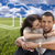 hispanic couple sitting in grass field with ghosted house behind stock photo © feverpitch