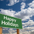 happy holidays green road sign over clouds and sky stock photo © feverpitch