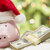 Pink Piggy Bank Wearing Santa Hat Near Stacks of Money on Snowfl stock photo © feverpitch