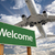 welcome green road sign and airplane above stock photo © feverpitch